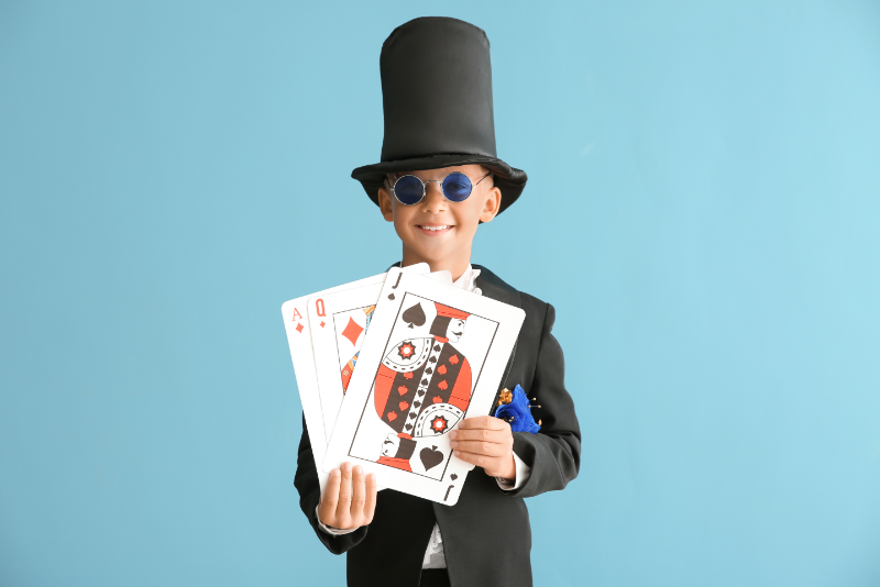 Boy in a magician's suit holding up a deck of cards smiling