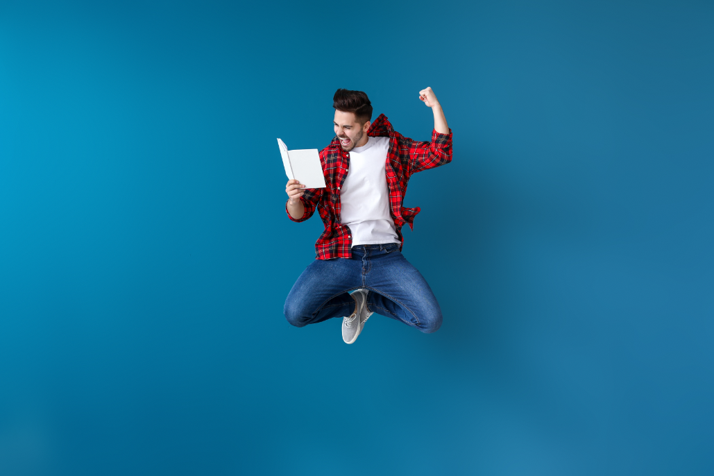 A man jumping in the air holding a book