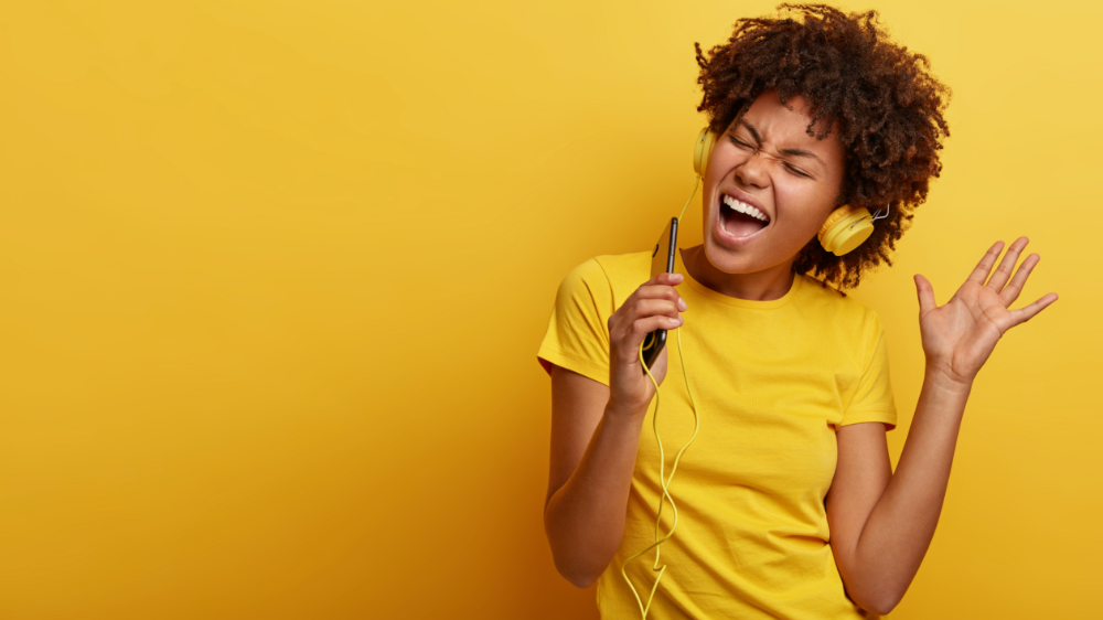 Woman in a yellow t-shirt singing into a microphone against a yellow background